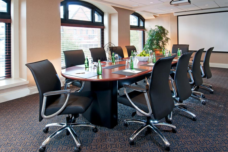 Boardroom table in center of room with natural light from large windows. Projector screen at end of table. Green apples on table with bottles of sparkling water.