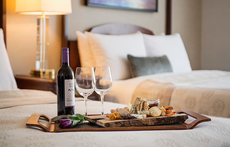 Bottle of red wine with 2 glasses by a selection of fine cheeses, crackers and tasting items on a wood platter on edge of queen sized bed in a room with 2 queen beds.