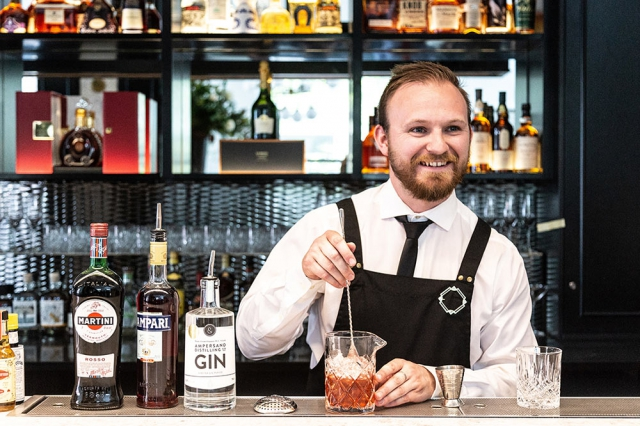 Bearded bartender mixing an old fashion in a bright lit modern bar