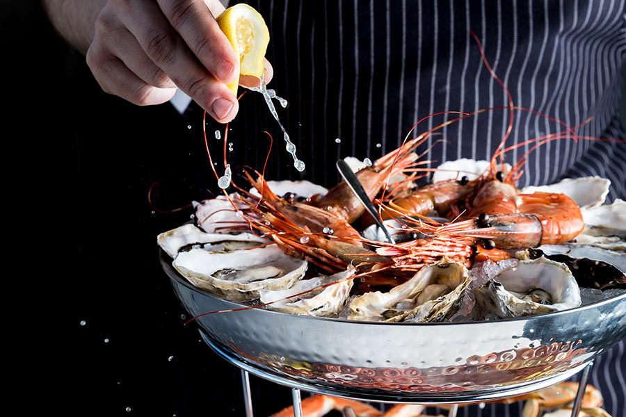 Juicy lemon squeezed over fresh seafood, prawns and oysters