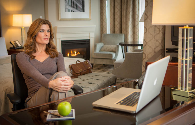 Women in front of laptop looking outward with leather bag on stool and fireplace on in background. Green apple on desk.