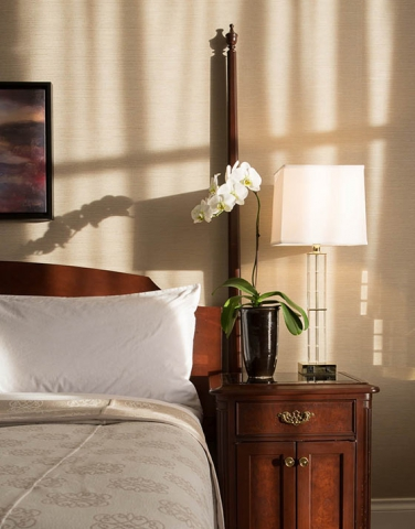 Magnolia Room bathed in sun, orchid on bedside table