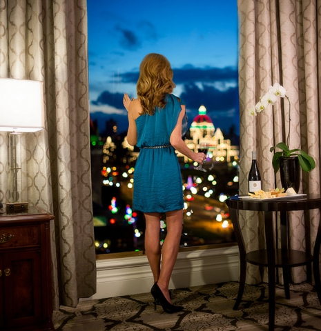 Women in evening cocktail style dress standing in front of floor to ceiling window with a perfect view of Victoria Parliament buildings at night, lit up with colorful lights. Bottle of winde and cheese plate on table with white orchid.