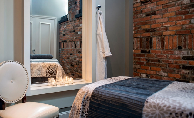 Magnolia Spa treatment room with brick wall, candles and house.
