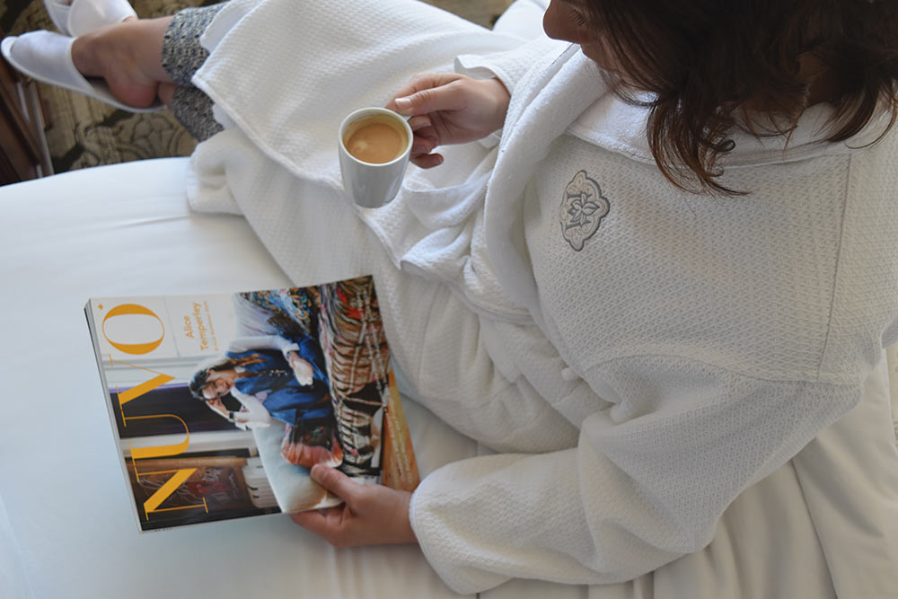 Women drinking Nespresso while reading NUVO magazine in bed, wearing Magnolia embroidered house coat.