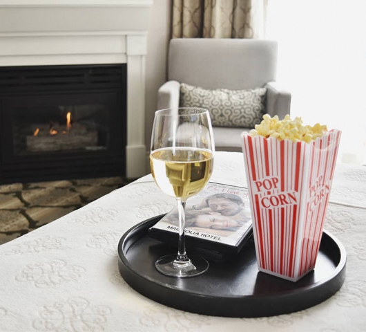 Popcorn, glass of wine and dvd movie on tray on edge of bed with warm fireplace in background