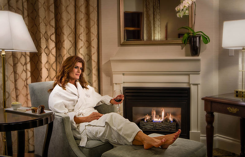 Relaxing in housecoat with wine by fire, room service plate on side table