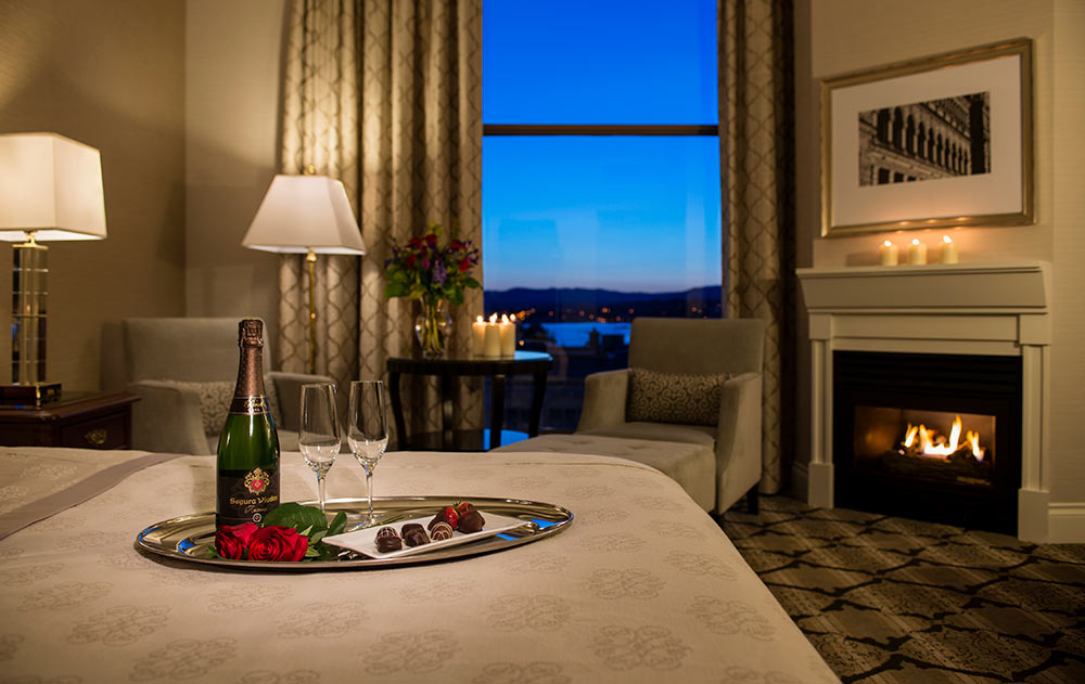 Champagne with 2 glasses on tray with chocolate and chocolate covered strawberries with a fire in fireplace and evening view of inner harbour.