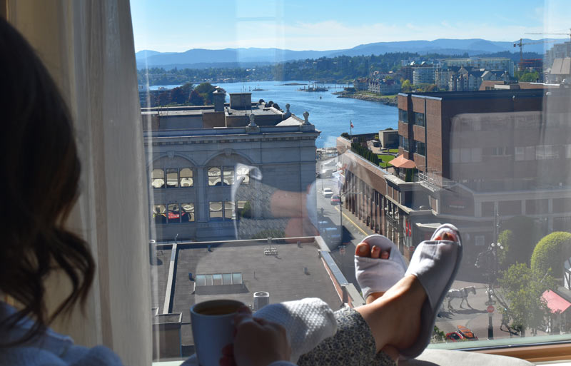 aha moment, women with slippers, feet, drinking coffee looking out grand window with view of water, buildings, and Victoria life.