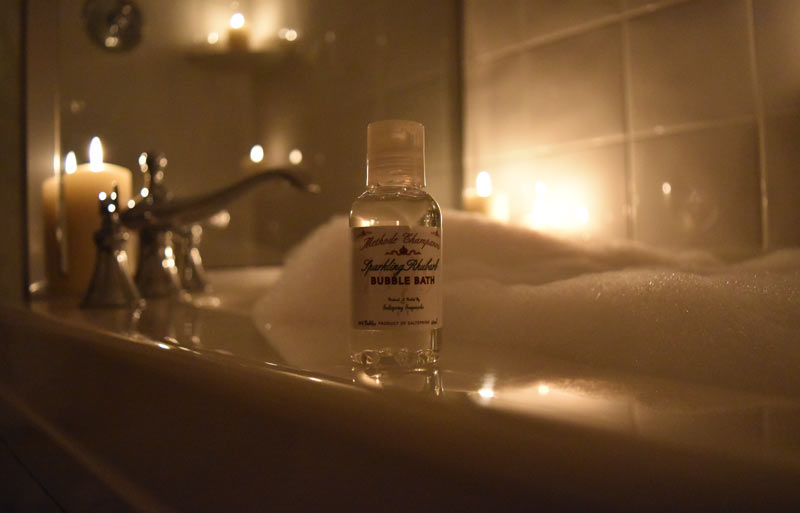 Bottle of hotel size bubble bath with deep soaker tub full of bubbles and candles in behind