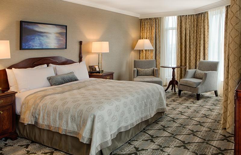 Deluxe corner room, queen size bed, sitting area, large floor to ceiling windows.