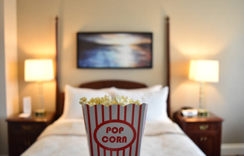 Large red and white container of buttered popcorn in front of 2 post bed in the background